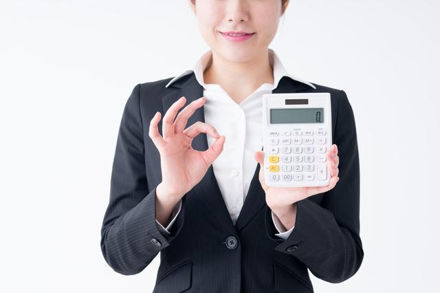電卓を持ちOKサインをする女性